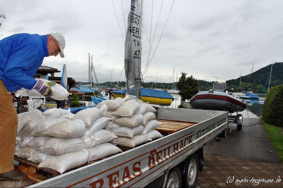 Beim Yacht Club Bad Wiessee werden von fleissigen Helfern die Sandsäcke wieder aufgeladen.