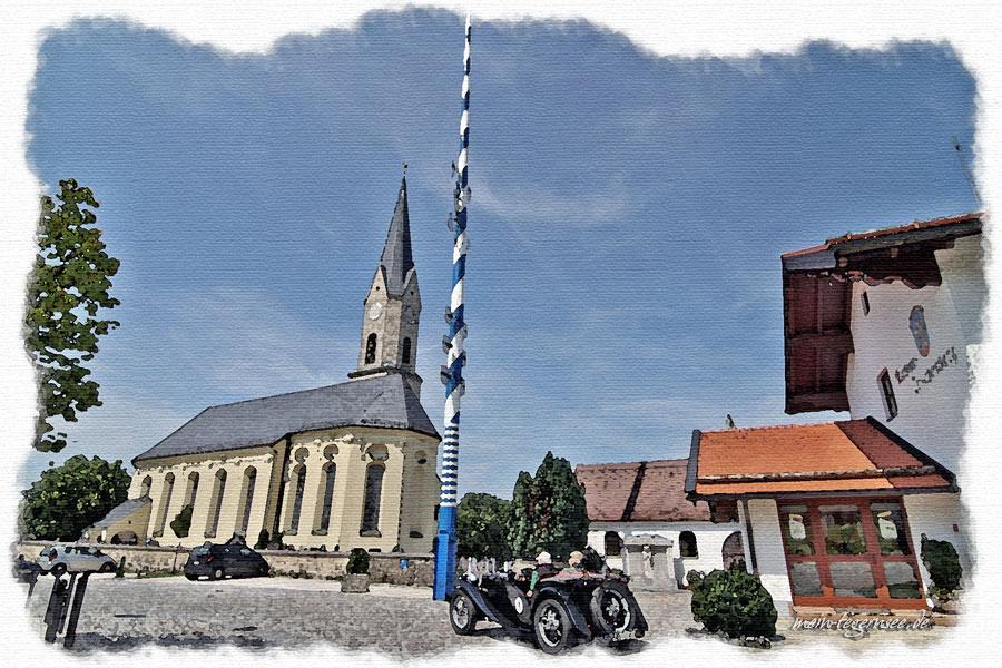 Rechts das Rathaus von Irschenberg und Blick auf die Pfarrkirche von Irschenberg, dem heiligen Johannes dem Täufer geweiht.