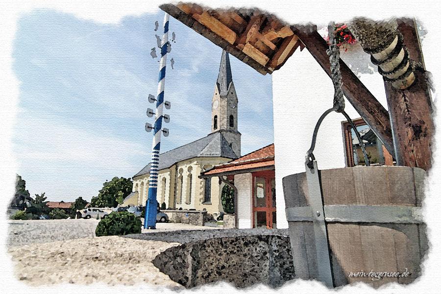 Blick über den Kirchplatz von Irschenberg mit dem Maibaum.