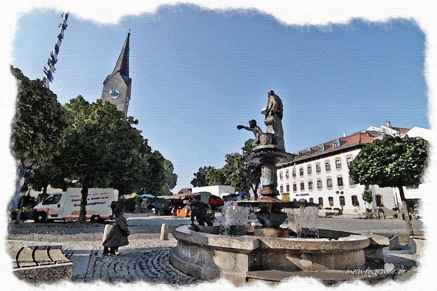 Blick auf den Marktplatz von Holzkirchen. Im Vordergrund der Brunnen zum Gedenken an den Bau eines Tiefbrunnens durch den Tegernseer Abt Kaspar Ayndorfer. Im Hintergrund die Kirche St. Laurentius.